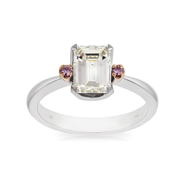 """Superbly crafted in 18 carat white gold, this engagement ring features an extraordinary Emerald Cut Diamond, whose beauty is enhanced by the perfectly matched pair of Pink Diamonds on either side. Created for the """"Classic Woman"""" who likes a point of difference."""