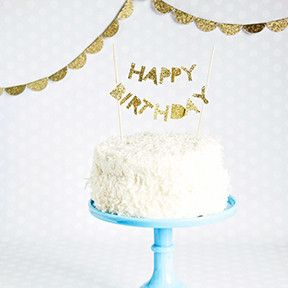 """""""Happy Birthday"""" cake topper made from letters hand-cut from gold glitter cardstock paper and strung onto white cotton twine, then attached to food-safe bamboo"""