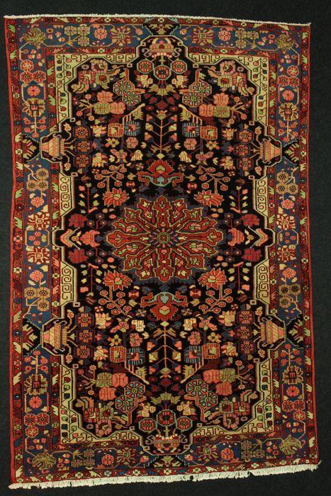Perzische Nahavand tapijt Iran.  Denominatie: Nahavand.Herkomst: Iran.Afmetingen: 293 x 194 cm.Alle wol met traditionele patronen: een centrale medaillon met veren motieven en achtergrond versierd met vazen en bloemen.Nahavand: met betrekking tot hun ontwerp deze tapijten zijn vooral geïnspireerd door de beroemde stad van Malayer verder west gelegen. Ze zijn stabiel met nomadische en geometrische element ontwerpen en zijn geclassificeerd onder de beste tapijten gemaakt in deze regio.Te koop…
