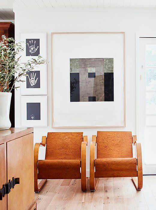 Jon Groom's Evidence of Monk #2 hangs above a pair of Alvar Aalto armchairs, creating a visual divide between the living room and the dining area. The three hands, photographed by Gary Schneider, are those of Laura, Cloud, and their daughter, Tess, when she was born.