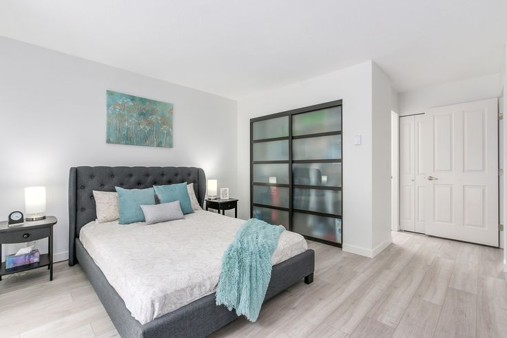 Spacious bright bedroom with teal colour accessories and a wardrobe that has glass sliding doors