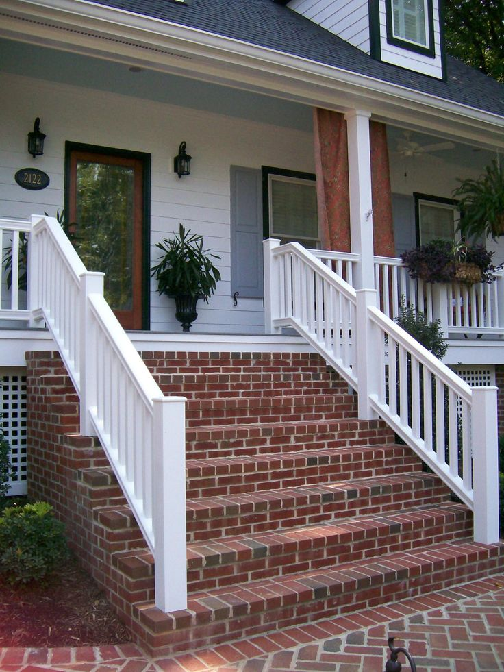 Red brick steps provide contrast to the bright white home exterior. The porch features a wood front door with a large window, and a blue-painted porch ceiling. Blue porch ceilings are a Southern tradition that supposedly help keep bugs away.