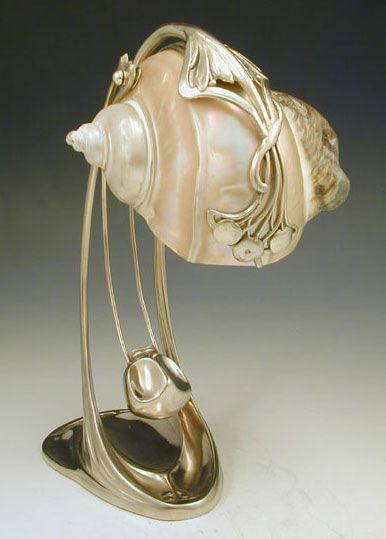 Manufacturer	Moritz Haker  Designer	  Description	Silver plate on pewter desk lamp with art nouveau floral decoration and a nautilus shell shade  Country of Manufacture	Germany  Date	c.1900