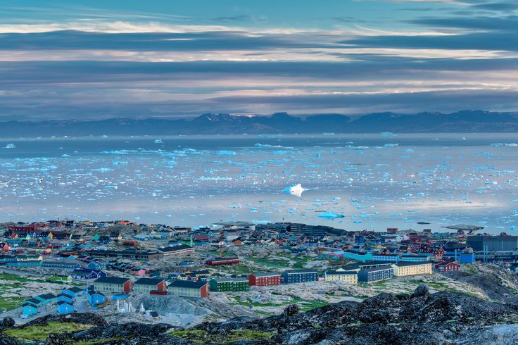 A view over the town of Ilulissat out over Disko Bay towards distant mountains, Greenland.