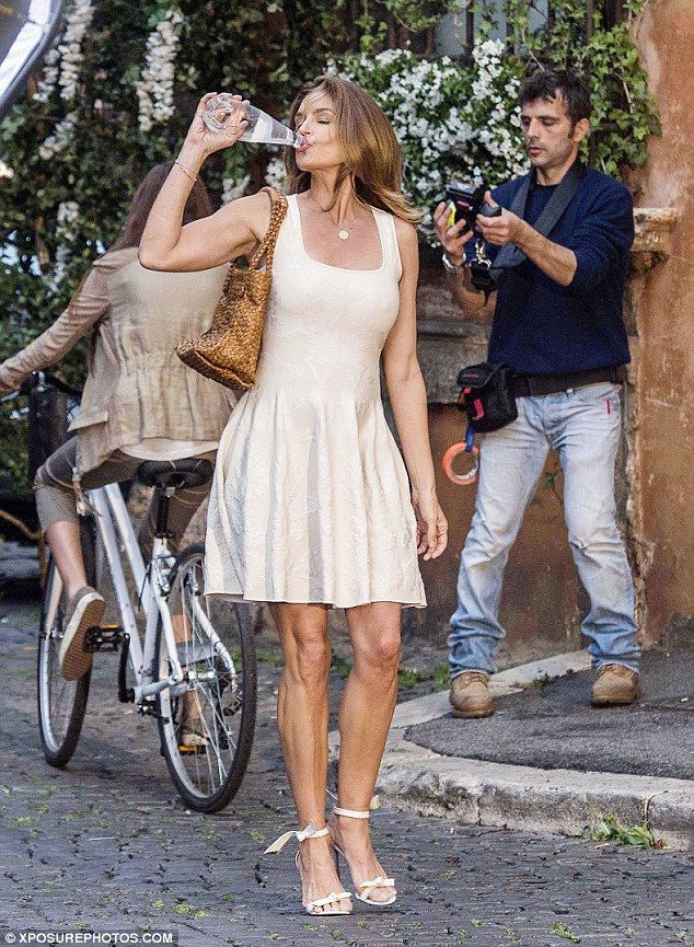 Still got it: Cindy Crawford looks sensational in an ivory dress as she shot an advert for San BBenedetto in Rome, Italy on Wednesday