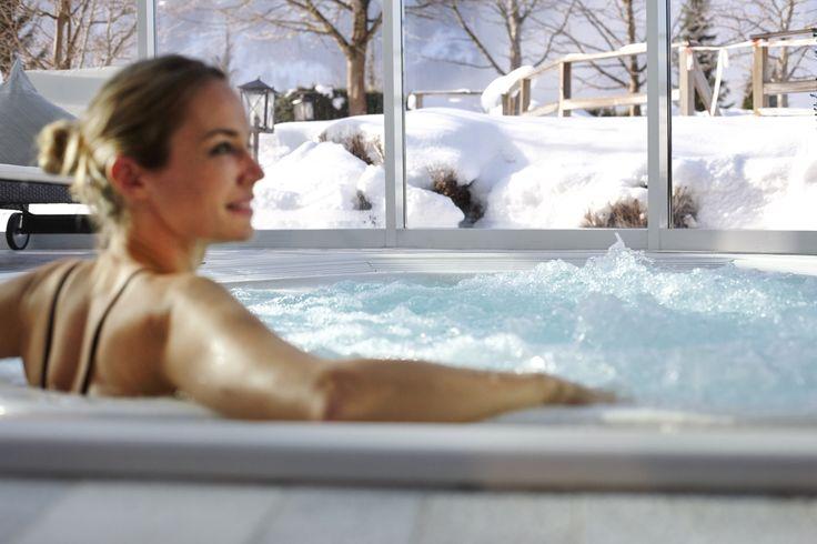 Der Hot Whirlpool mit Panoramablick auf die Salzburger Bergwelt im Alpin Spa. Das Wellnesshotel Oberforsthof im Alpendorf.