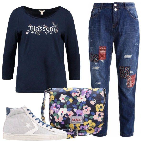 I jeans sono larghi sui fianchi, hanno le toppe colorate, con la semplice maglietta con scritta, le sneakers alte e la borsa tutta fiorata, donano un'aria anni '90.