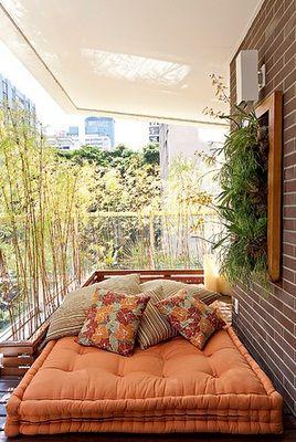 Olha que graça este futon jogado no deck com um monte de almofadas, o mini jardim vertical e a parede de mini bambus
