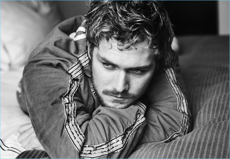 Stealing a quiet moment, Finn Jones wears a jacket and pants by Gucci.
