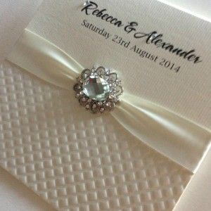 Wedding invitation using Indian Embossed Diamonds paper in Pearl color. Beautiful detailing with the ribbon and stone!