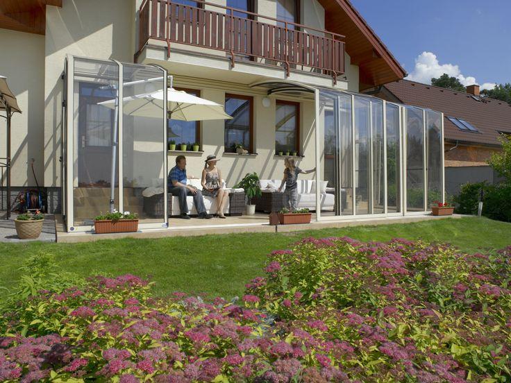 Posuvné zastřešení terasy CORSO v bílé barvě skvěle ladí k přilehlému domu.