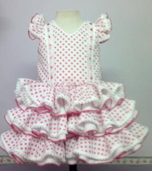 Traje de gitana flamenca para bebe en popelín rosa fucsia con lunares pequeño blanco adornado con madroños blancos. Disponible bolsito y lazo a juego.  Todos nuestros trajes de gitana son totalmente personalizables, preguntanos en mibebesito@mibebesito.es