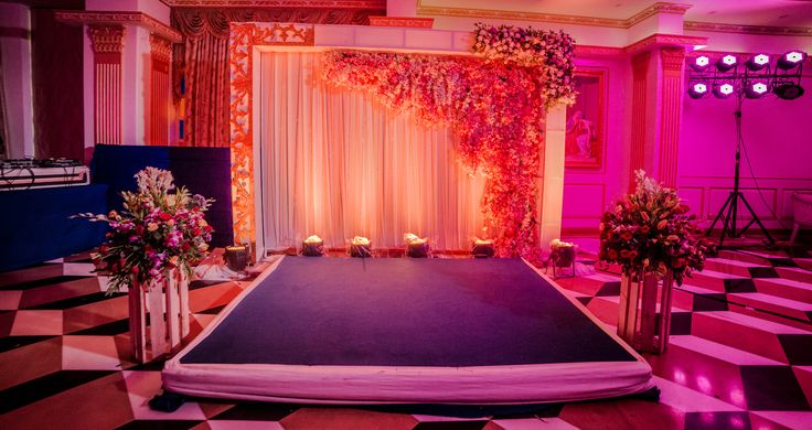 Sangeet stage for bride and groom. Elegant flowers. Evening party