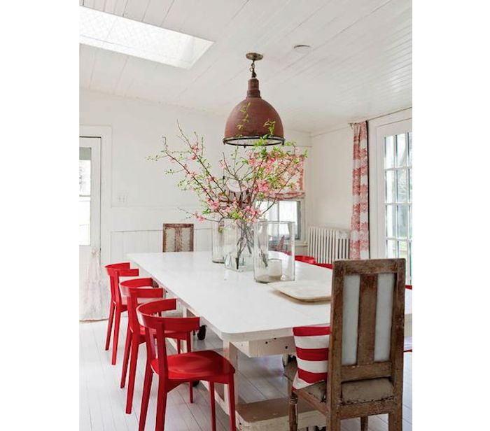 Love the curtains, and the industrial fixture...they make the stark white walls and modern red chairs less harsh and more live able.