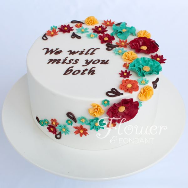 red, yellow, orange & aqua ruffle flowers on a farewell cake.