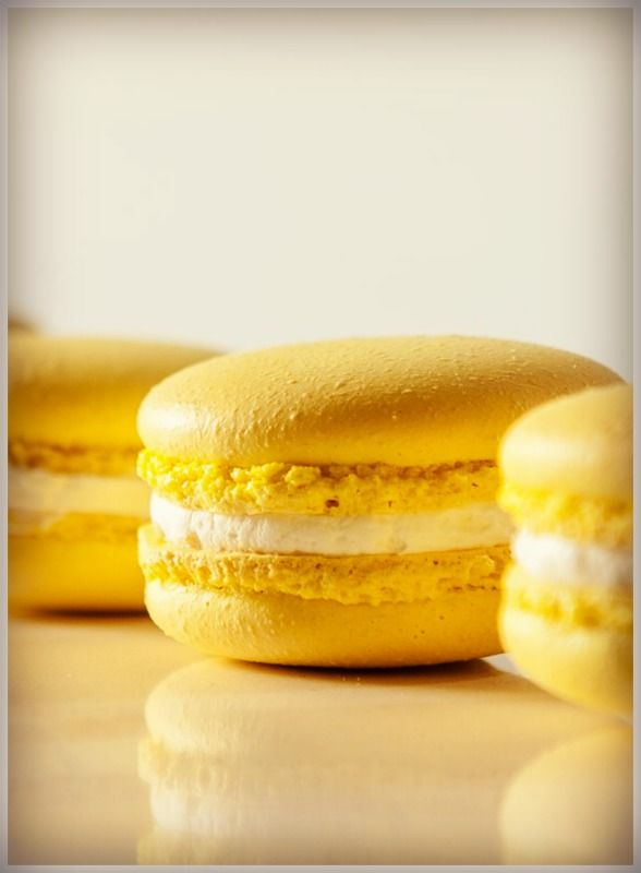 These Lemon Macarons offer you the tastes and textures of cookie poetry. Your first bite cracks the crisp, egg-like shell. Lemon buttercream rushes your taste buds with sweet drama. Your second bite reveals a tart lemon curd center, as delicious as a classic line in Shakespeare.