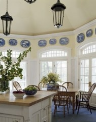 In a Southern-style home, there is plenty of room to eat in the kitchen. A large dining table is a must. Love the cherry wood, white trim, blue and white dishes and yellow walls seen here.