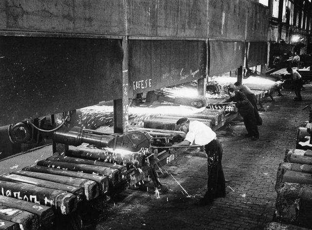 Interieur van de walserij van de fabriek van de N.V. Nederlandse Staalfabrieken DEMKA voorheen J.M. de Muinck Keizer (Havenweg 7) te Utrecht: de blokbaan tijdens het afslijpen van gietscheuren in de walsblokken, het z.g. blokkenpoetsen. 1964