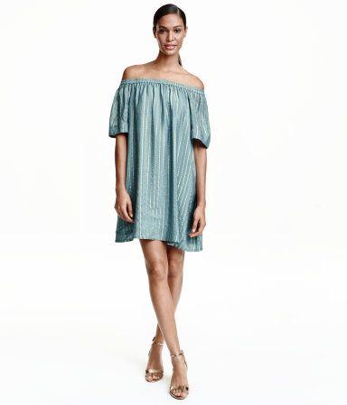 Tåkeblå. PREMIUM QUALITY. En utsvingt off-shoulder kjole i silke med striper av glittertråder. Kjolen har elastikk øverst og korte, vide ermer. Fôret.