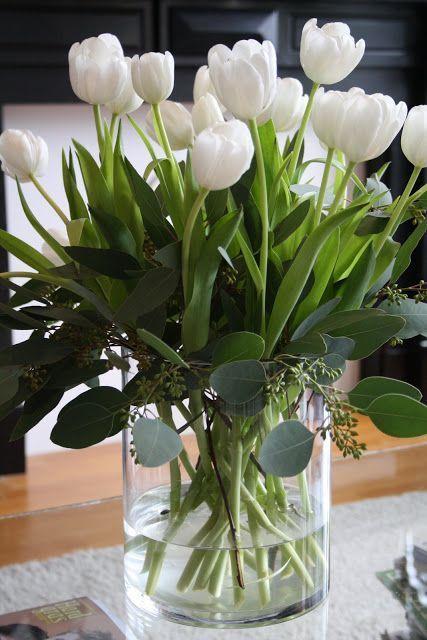 Exquisite white tulips in glass vase.