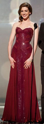 After walking the red carpet in the favorite hue of the night, Hathaway took to the stage in slightly different version of red — a burgundy silk chiffon gown by Atelier Versace, with Tiffany jewels and Casadei pumps.
