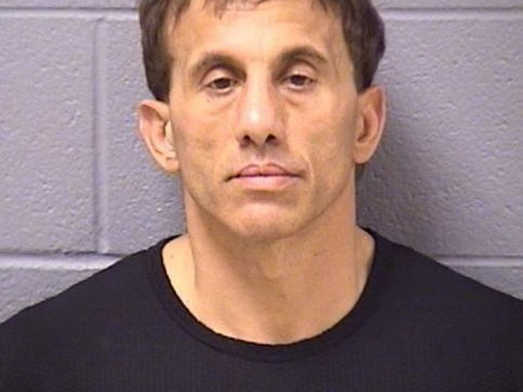 The cheerleading coach was arrested at his job in Aurora, police said.