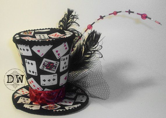 Welcome and thank you for your interest!    Listed is a mini top hat crafted by hand by myself!    This hat stands 4 inches tall, and measures approx. 5 inches across the brim.    The hat is covered in a black fabric with playing cards on it. I do NOT use felt, newspaper or cardboard at all in the construction of the hat. On the front of the hat there is black netting and black feathers all held together by a black flower. There is a red sheer ribbon with a little glitter print around the…
