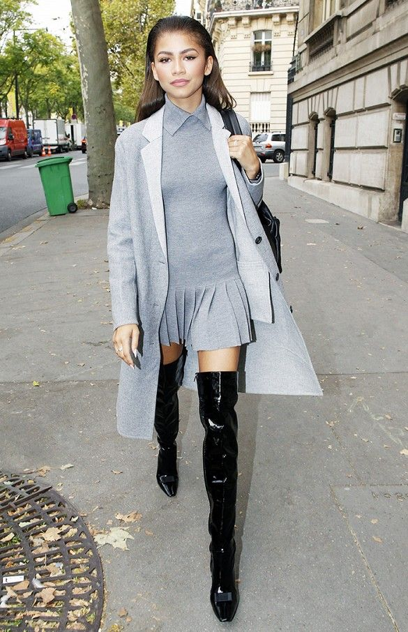 Zendaya wears a pleated minidress, gray coat, and thigh-high patent leather boots: