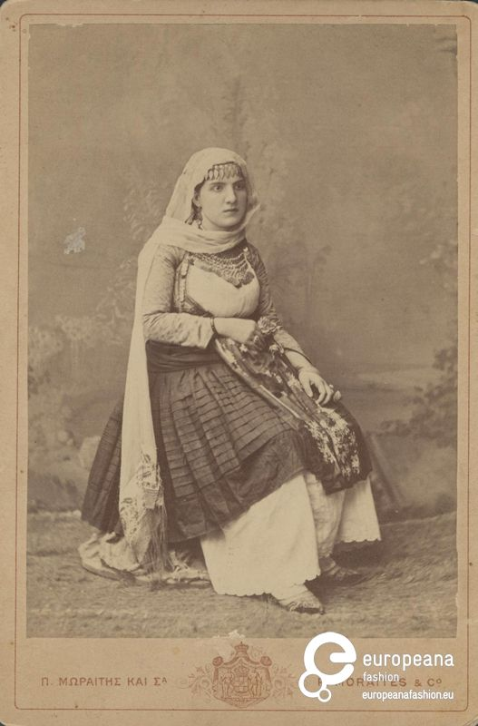 "Photo B/W photo of a woman with local costume from Megara, Greece. Inscriptions: ""Π. ΜΩΡΑΪΤΗΣ ΚΑΙ ΣΙΑ"", ""P.MORAITES & Co"".. 1880-1900"