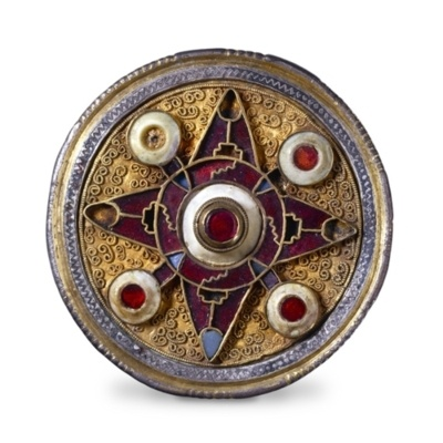 A 7th century Anglo-Saxon disc brooch made with gold plate, garnets, and shell.