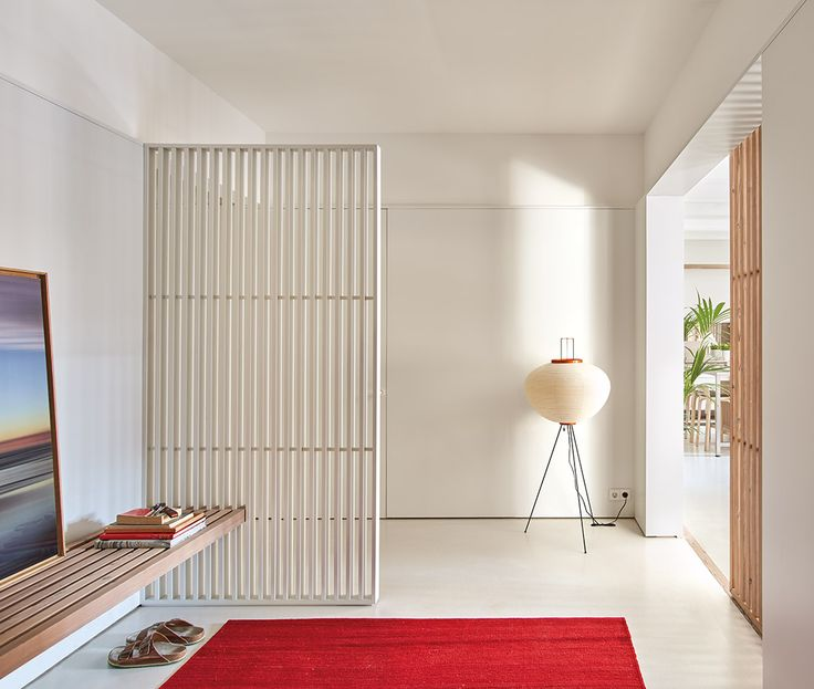 En el vestíbulo, banco de madera de pino de Flandes aceitado blanco; lámpara de pie Akari 10A, de Isamu Noguchi, editada por Vitra, y la alfombra, de lana de Afganistán, modelo Nomad Grana, de nanimarquina