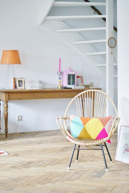 {wood & wool harlequin} fabulous rattan chair + harlequin-patterned pillow! LOVE this.
