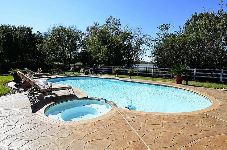 Kidney-shaped pool with adjoining spa in a country setting
