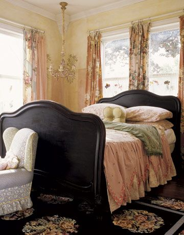 Myriad patterns come together in this feminine room, from the slipper chair upholstered in a rainbow of fabrics to the bedspread fashioned from a variety of floral linens. A floral-motif chandelier hangs in one corner, against a wall adorned with a stencil of water lilies and irises. Propped against the shams, a pert petal pillow.