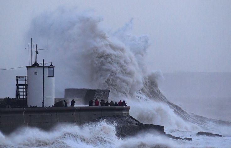 3 de janeiro - Pessoas são vistas ao lado de ondas gigantes e ventos fortes associados com a tempestade Eleanor no farol e paredão em Porthcawl, no sul do País de Gales (Foto: Toby Melville/Reuters)