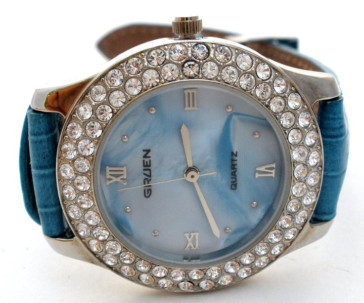 Fashion Watches - This is a pre-owned Gruen watch with a mother of pearl face, surrounded with clear rhinestones and a blue leather band. It has a new battery and works properly. The watch case measur