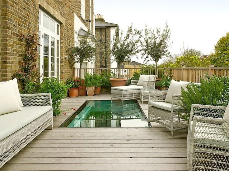 Fabulous outdoor deck with soaking tub framed by terracotta potted plants- beautiful retreat!