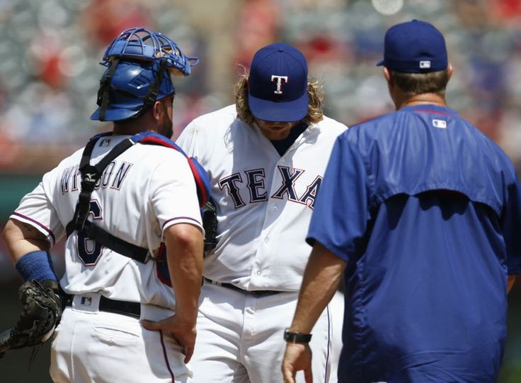 Texas Rangers starting pitcher A.J. Griffin, catcher Bryan Holaday (8) and pitching coach Doug Brocail meet on the mound  during the fifth inning Sunday, July 10, 2016, in Arlington, Texas. (AP Photo/Jim Cowsert)