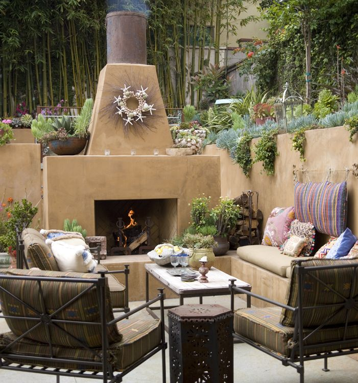 The styling around this outdoor fireplace is absolutely stunning. Love the wreath, the plantings spilling over the edges of the walls, and the water-wise container plantings. From Sandy Koepke Interior Design.