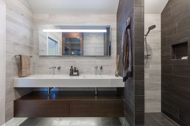 In the ensuite, a  custom-designed dual-basin unit sits atop a simple timber oblong vanity, with an open space between for towel storage