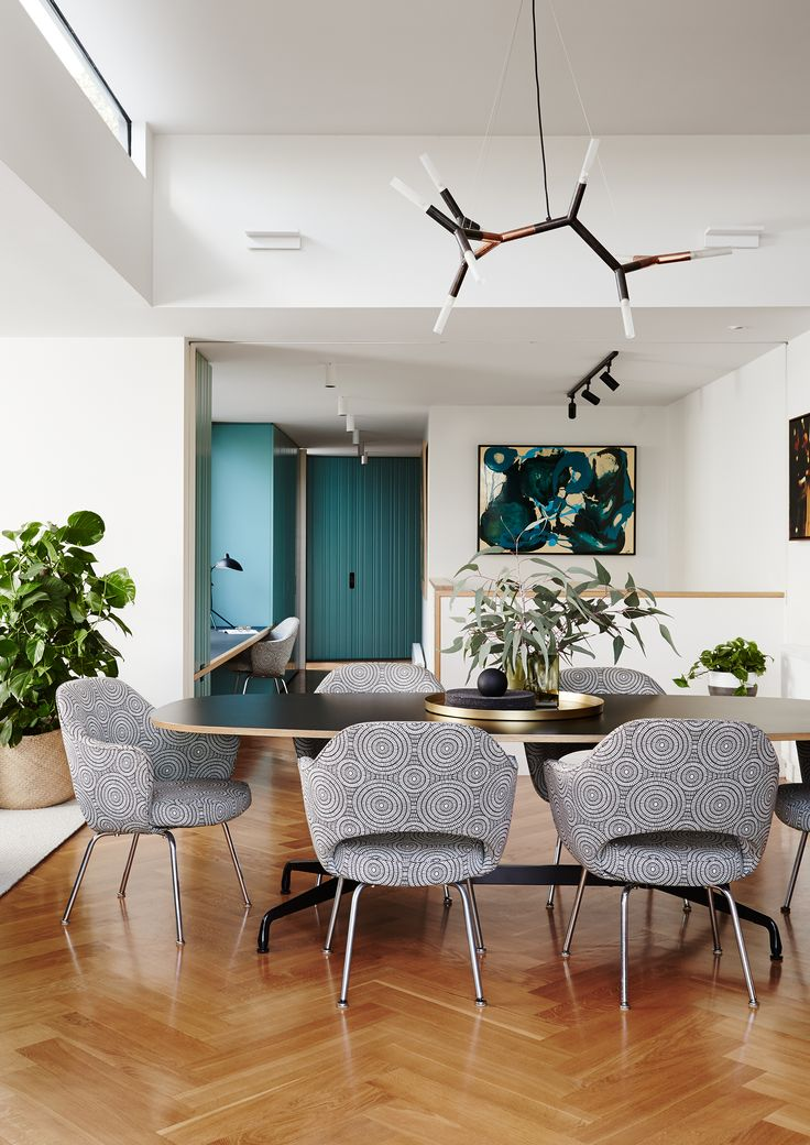 Modernist dining room with upholstered chairs, herringbone floor and teal accents in Melbourne inner south-east home. Photography: Annette O'Brien | Stylist: Becky Littler | Story: Australian House & Garden