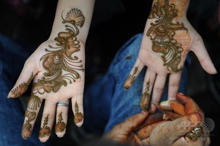 インド・ムンバイ(Mumbai)で、断食月「ラマダン(Ramadan)」の終わりを祝う祭り「イード・アル・フィトル(Eid al-Fitr)」に先立ち、露店で「ヘナ」と呼ばれる染料を用いた絵柄を両手に施してもらうイスラム教徒の女性(2014年7月28日撮影)。(c)AFP/INDRANIL MUKHERJEE ▼30Jul2014AFP|断食月ラマダン終了、世界各地で「イード・アル・フィトル」 http://www.afpbb.com/articles/-/3021766 #Mumbai