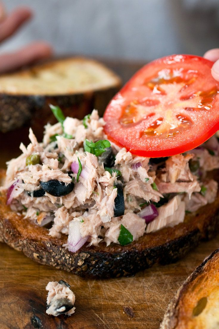 NYT Cooking: This is not your mother's mayonnaise-laden tuna salad, but it's just as easy to prepare. Here's what you do: stir together some canned tuna, garlic, lemon juice, red onion, black olives, capers and fresh parsley, then spread it on buttered toast. Top it off with a round of ripe tomato or slivers of avocado and another slice of toast. That's it. If you want to make%...
