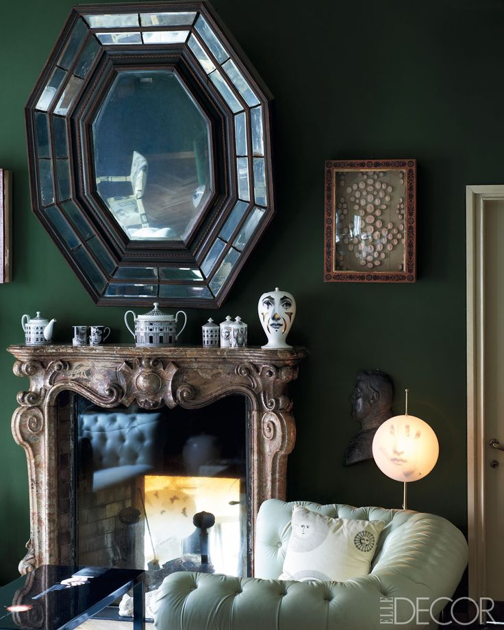 Deep green living room walls in Barnaba Fornasetti's Milan home.