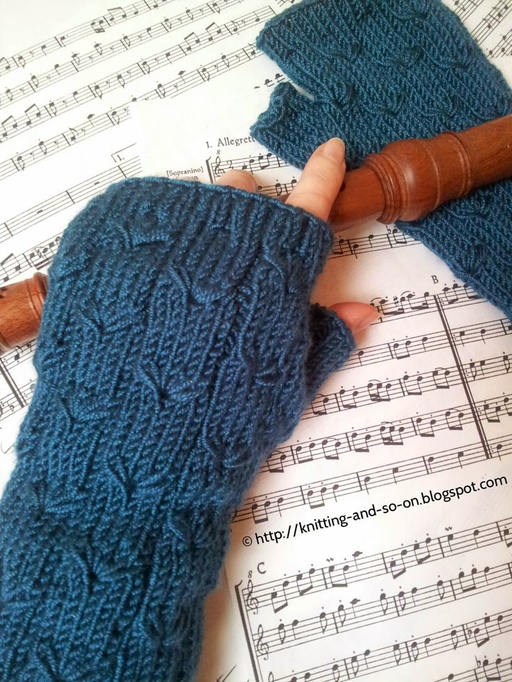 A pair of fingerless gloves with a flower pattern. The effect is achieved by drawing additional loops through stitches two rows below.   ...