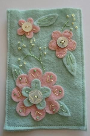 felt hand embroidered flower and mother of pearl buton mobile cosy. £7.50, via Etsy. by tamera