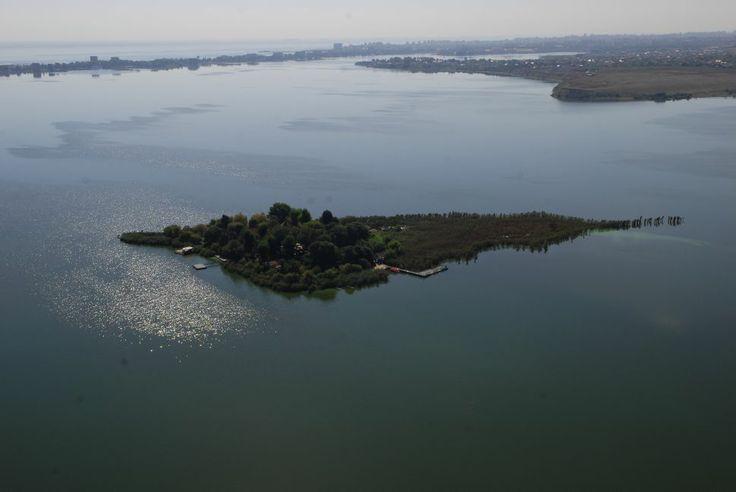 """INSULA OVIDIU  Insula Ovidiu este singurul obiectiv turistic de la noi din ţară care se află pe o insulă naturală. Amplasată pe lacul Siutghiol la 5000 de metri de malul staţiunii Mamaia şi la 500 de metri de cel al oraşului Ovidiu, este un loc inedit al litoralului românesc.   Poetul latin Ovidiu, exilat de împăratul Cezar, se pare că a locuit pe insula care îi poartă numele, unde a şi scris, de altfel, """"Tristele"""" şi """"Ponticele"""", inspirate de atmosfera mohorâtă a iernilor la malul mării."""