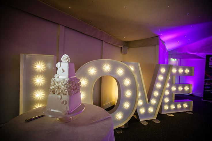 Highlight your wedding cake by positioning it next to light up letters.