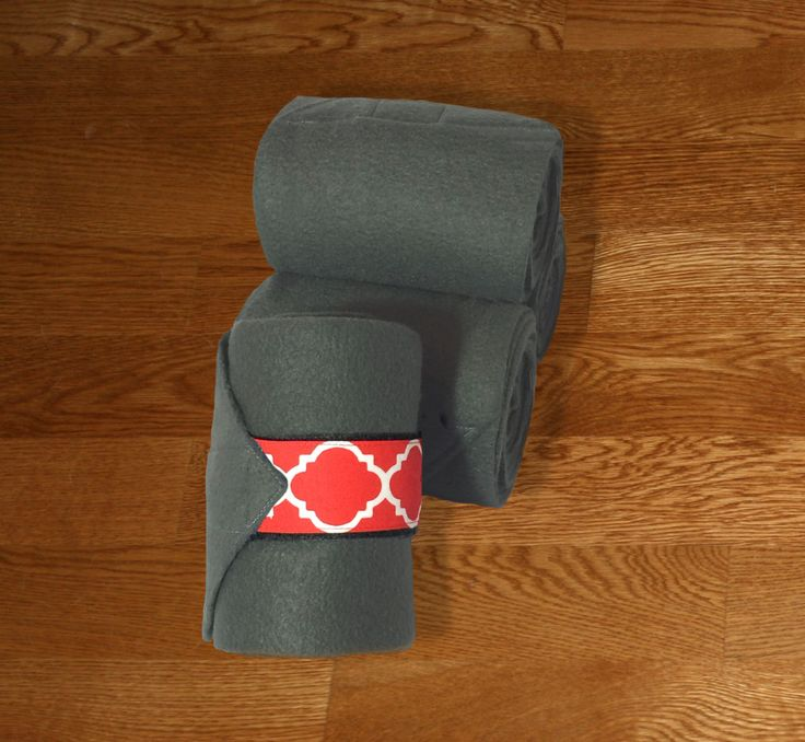 """Equine Polo Wraps/Gray Polo Wraps w/Red Quatrefoil Velcro Strap. Made with quality gray fleece and industrial strength velcro to ensure a proper hold. Two sizes offered: Pony: 2 yards (6ft) length, 4"""" wide Horse: 9 ft front, 11 ft hind length, 5"""" wide."""