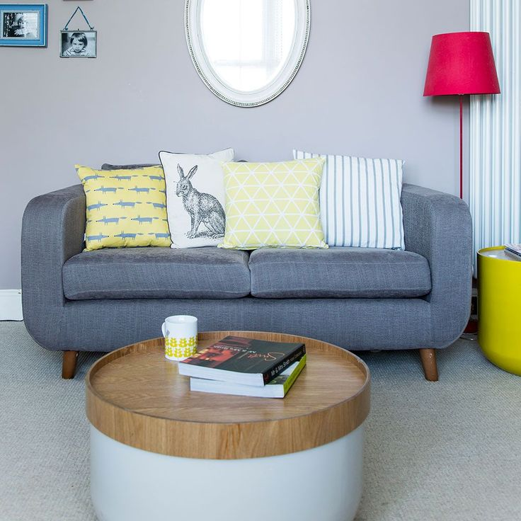 Bright living room design with grey sofa, pink floor lamp and round coffee table